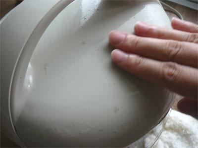 炊飯器にスプレーした洗剤液を指でなじませているところ